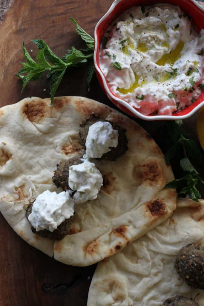Greek tzatziki sauce dollops on meatballs and pita